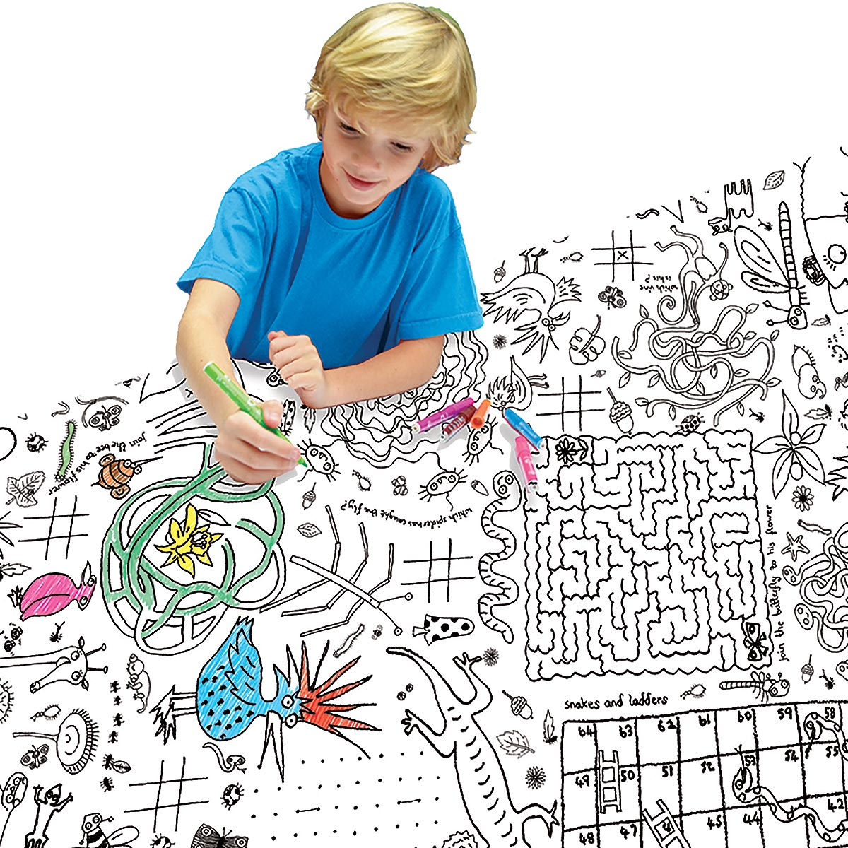 boy sitting at table colouring tablecloth