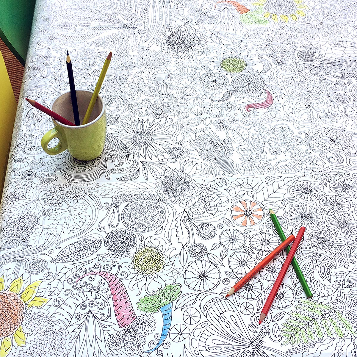 tablecloth partially coloured in with crayons in mug
