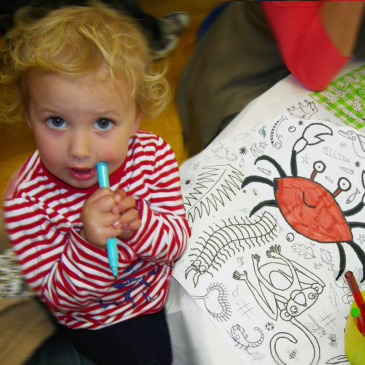 young child with pen at table with colour-in tablecloth
