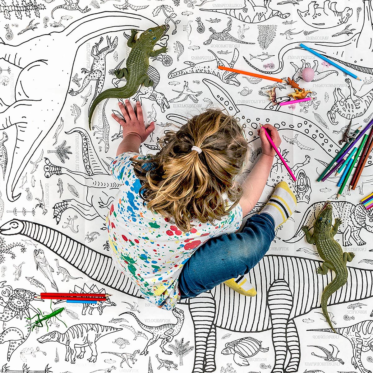 girl sitting on tablecloth on floor colouring
