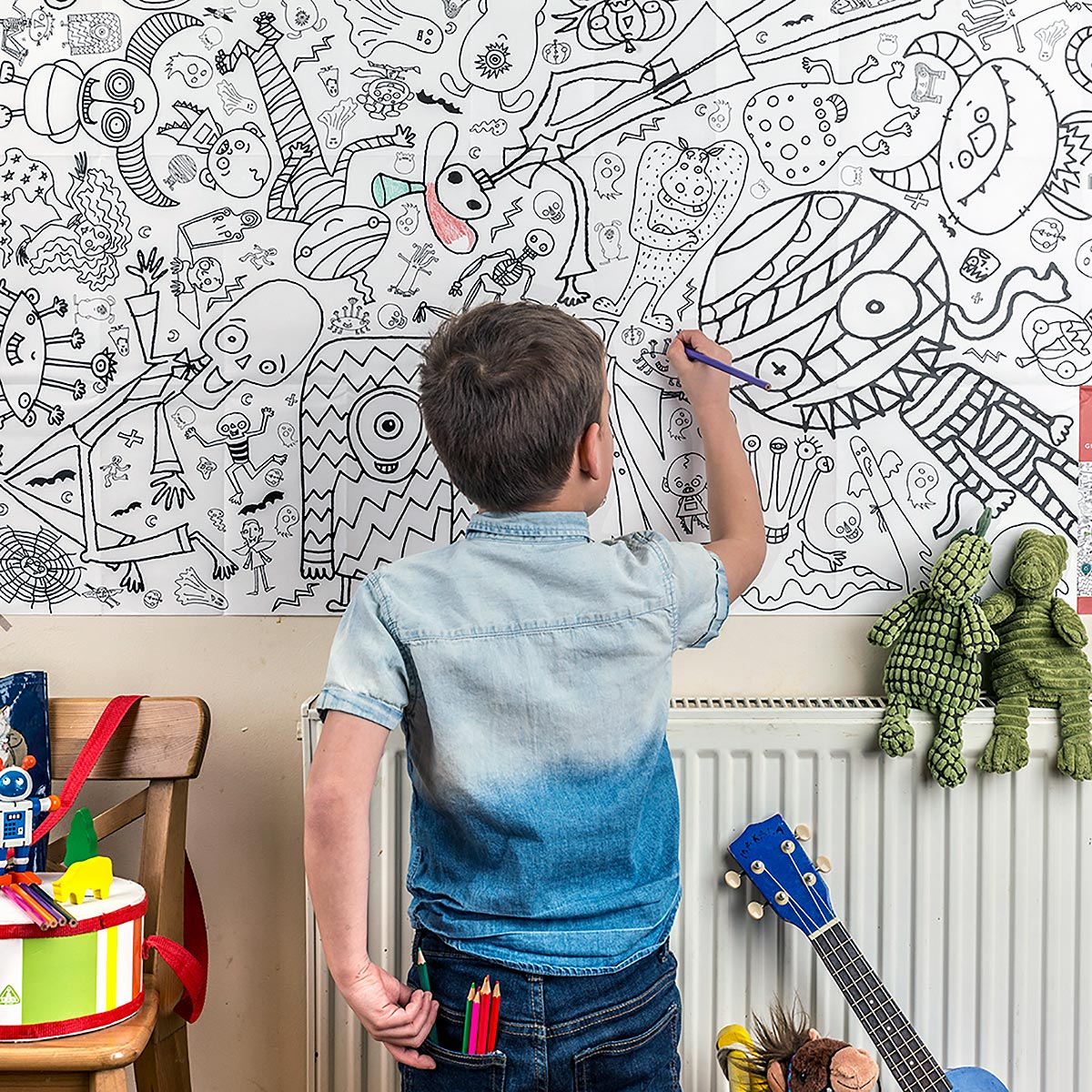 boy with crayons colouring in tablecloth hung on wall