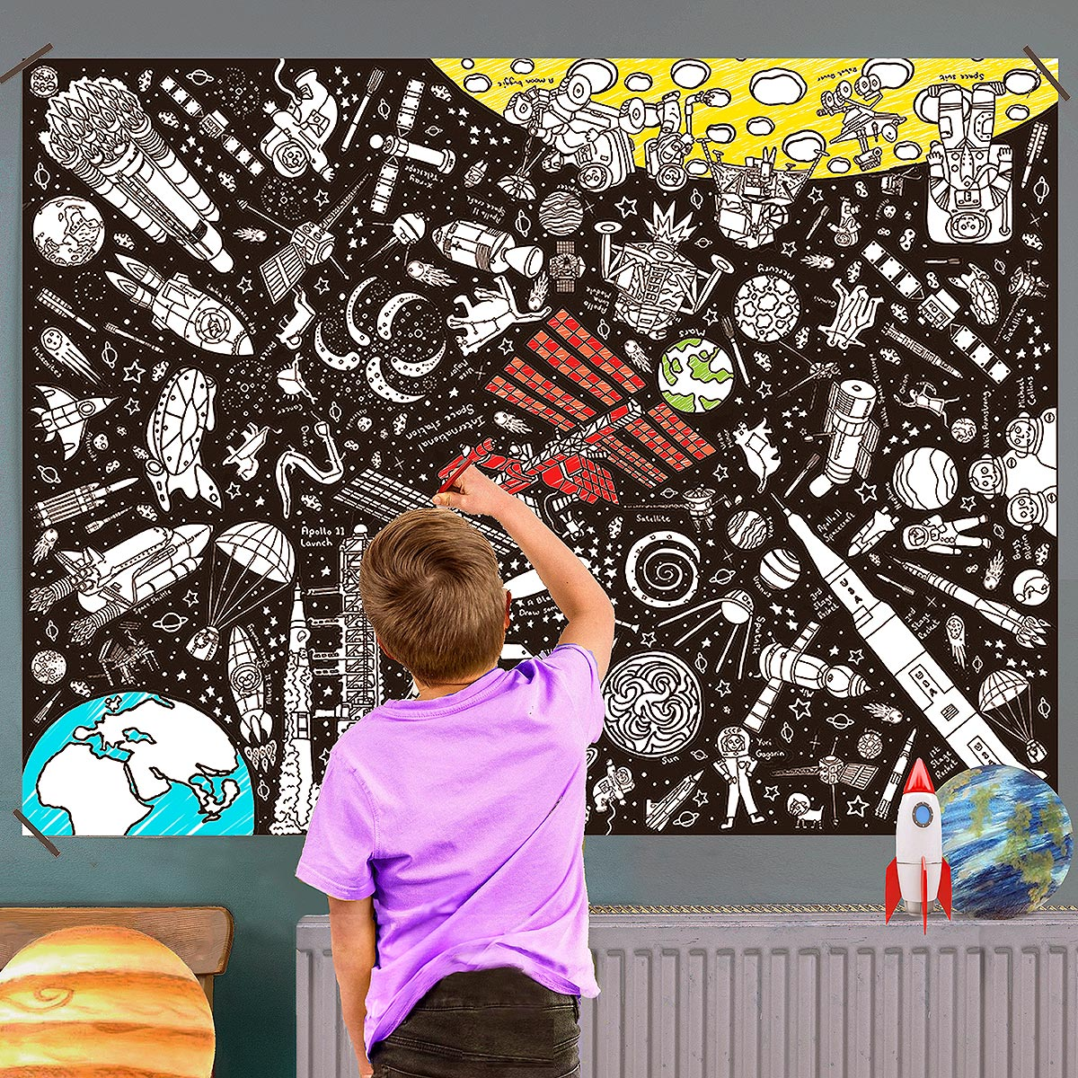 boy colouring in poster on wall
