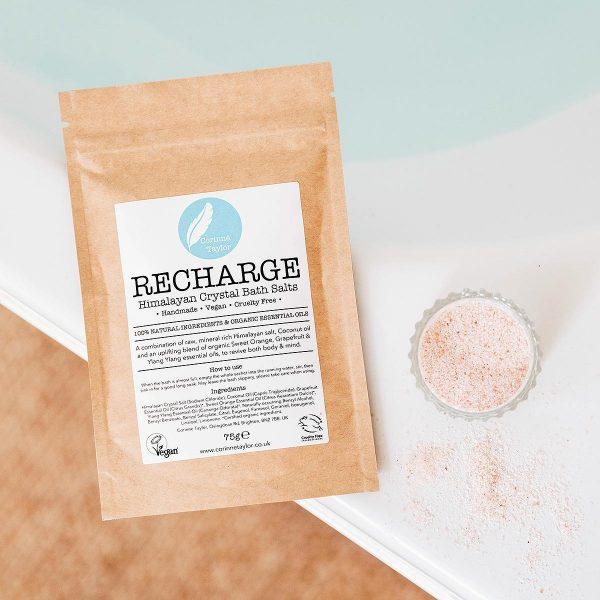 brown sachet of hot bath on edge of hot bath with loose pink bath salts
