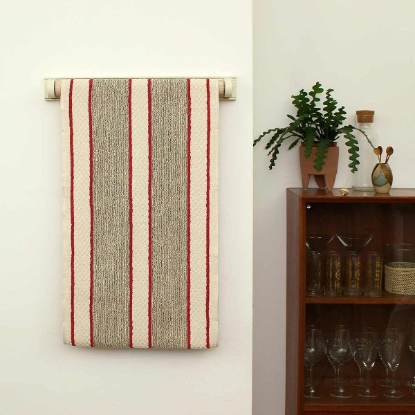 towel on rail on wall next to plant on cupboard