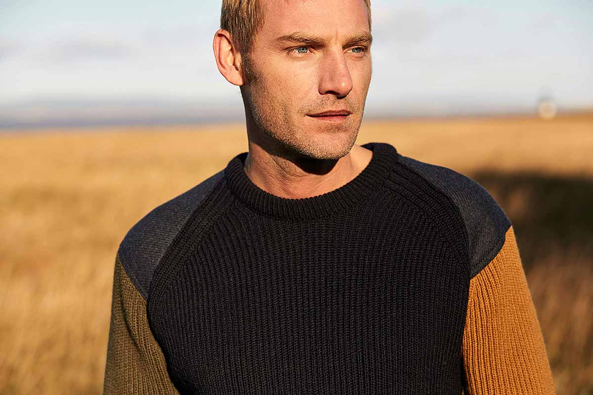 head and shoulders of man wearing jumper in field