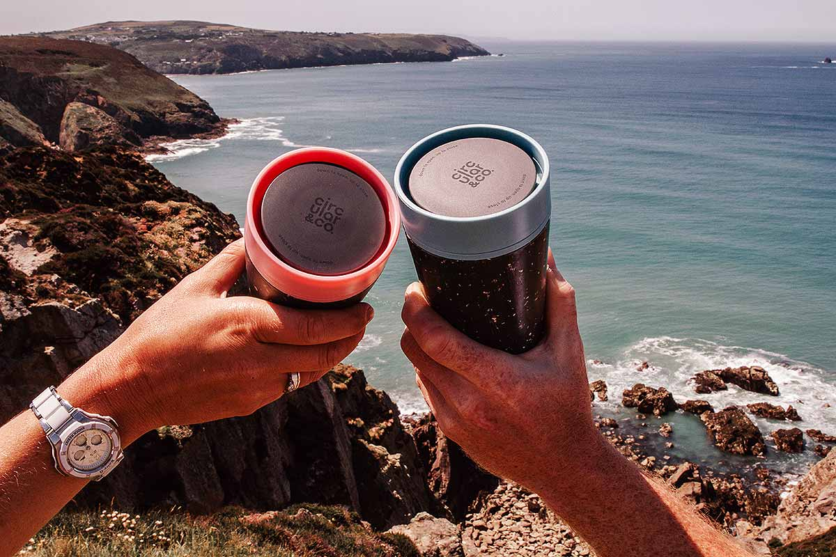 two hands holding cups overlooking sea and cliffs