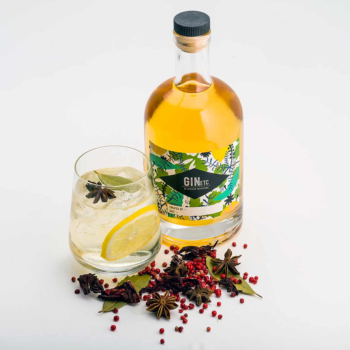 bottle and filled glass with botanicals on white background