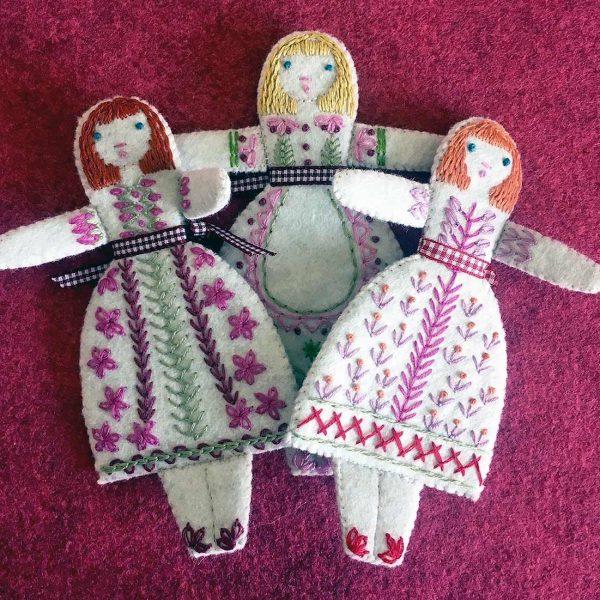 three felt dolls on ruby background