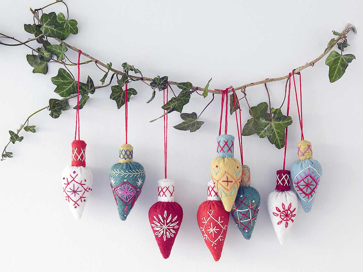 cones hanging from ivy garland on white background