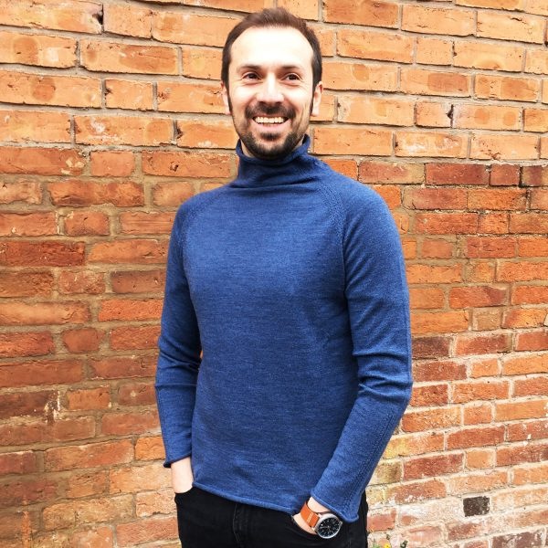 man wearing jumper in front of brick wall
