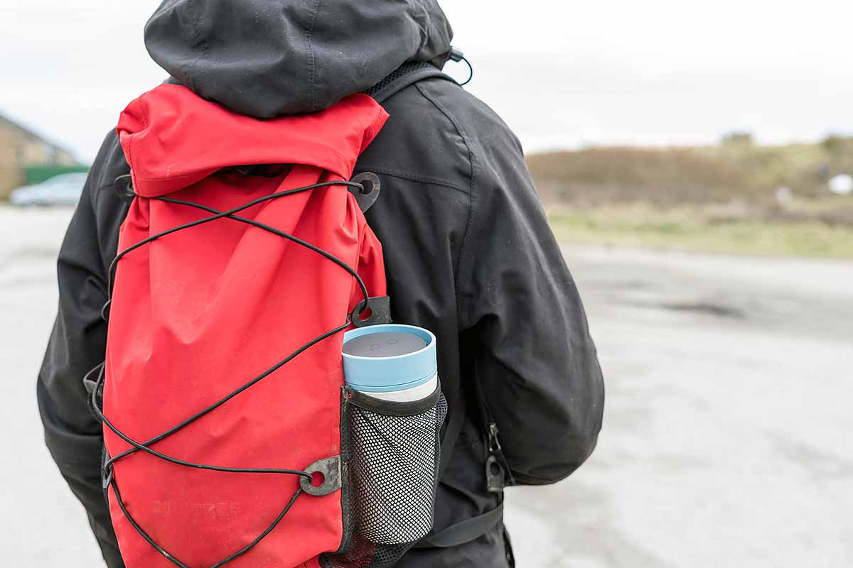 cup in rucksack on man's back