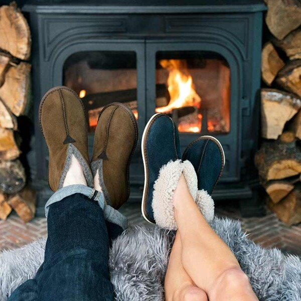 feet in slippers in front of roaring log burner
